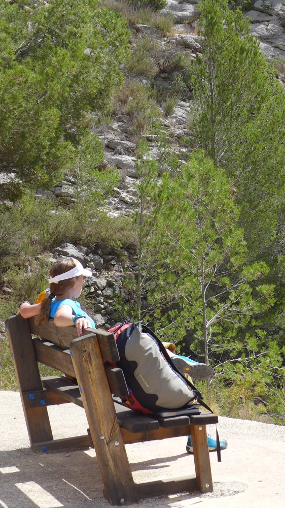 Person sat on a bench looking at the scenery, climbing bag next to them