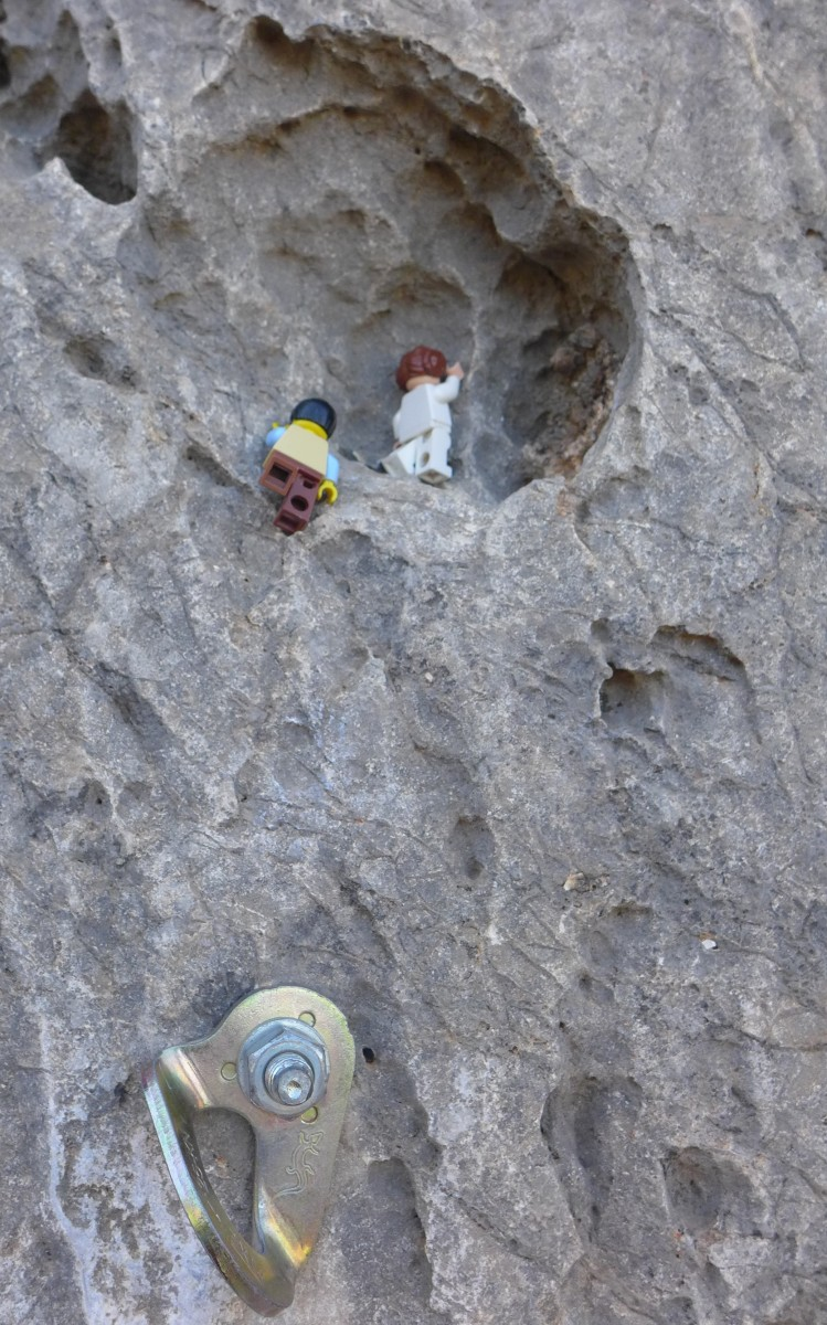 Lego figures climbing up some rock