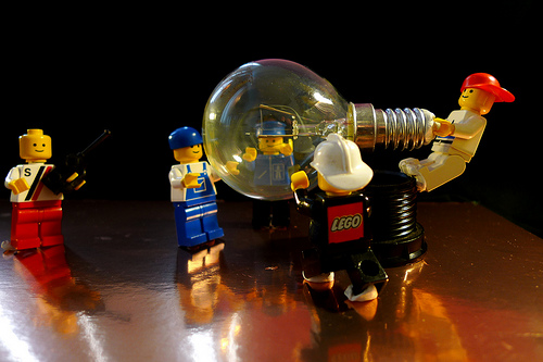 Lego figures collaborating together fitting a light bulb